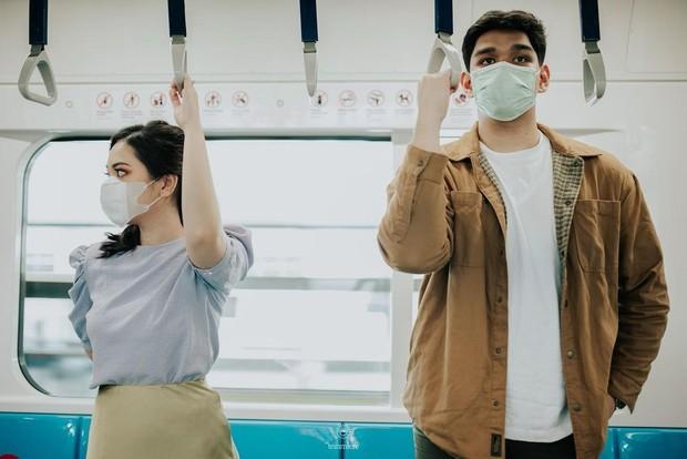 Nabila dan Harits berfoto di dalam rangkaian kereta MRT dan stasiun MRT. Keduanya mengikuti protol kesehatan, yakni mengenakan masker.
