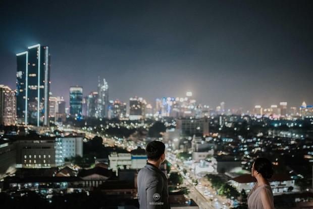 Nabila dan Harits berfoto di sebuah rooftop dengan latar belakang pemandangan gedung-gedung bertingkat dan lampu kota.