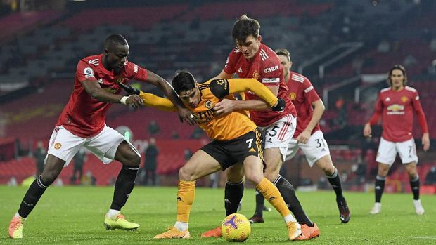 Wolverhampton Wanderers' Pedro Neto is challenged by Manchester United's Harry Maguire, right, during the English Premier League soccer match between Manchester Utd and Wolverhampton Wanderers at Old Trafford stadium in Manchester, England, Tuesday,Dec. 29, 2020. (Michael Regan, Pool via AP)