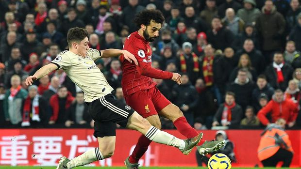 LIVERPOOL, ENGLAND - JANUARY 19: Mohamed Salah of Liverpool scores his team's second goal past David De Gea (not pictured) of Manchester United as he is challenged by Daniel James of Manchester United during the Premier League match between Liverpool FC and Manchester United at Anfield on January 19, 2020 in Liverpool, United Kingdom. (Photo by Michael Regan/Getty Images)
