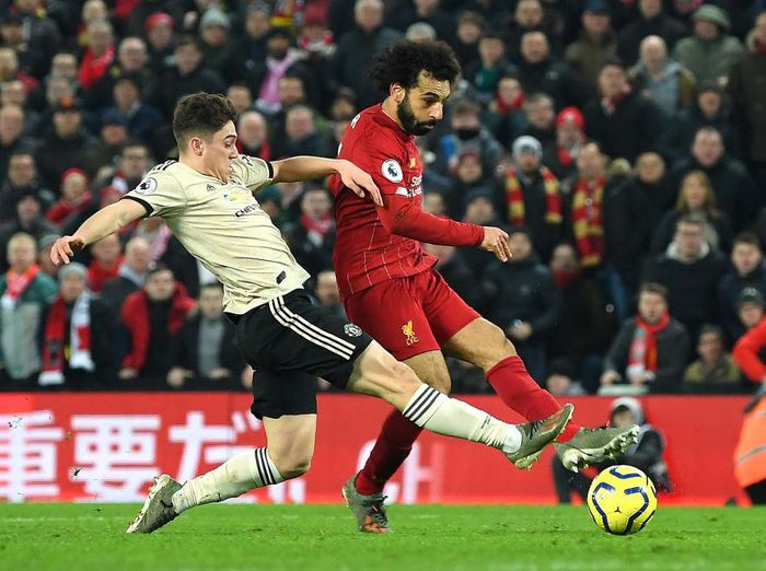 LIVERPOOL, ENGLAND - JANUARY 19: Mohamed Salah of Liverpool scores his teams second goal past David De Gea (not pictured) of Manchester United as he is challenged by Daniel James of Manchester United during the Premier League match between Liverpool FC and Manchester United at Anfield on January 19, 2020 in Liverpool, United Kingdom. (Photo by Michael Regan/Getty Images)