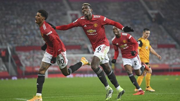 Manchester United's Marcus Rashford, left, celebrates with Paul Pogba after scoring the opening goal during the English Premier League soccer match between Manchester Utd and Wolverhampton Wanderers at Old Trafford stadium in Manchester, England, Tuesday,Dec. 29, 2020. (Michael Regan, Pool via AP)