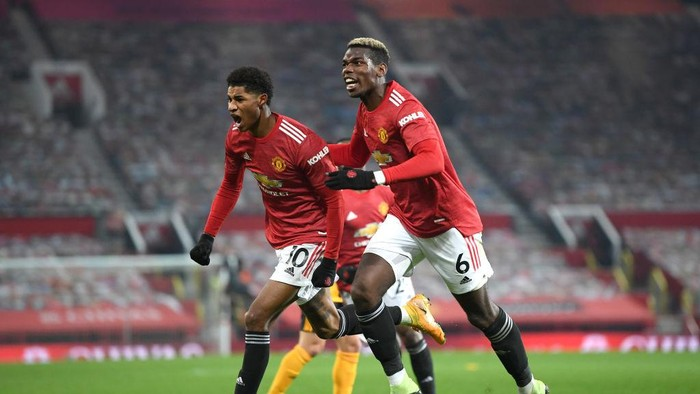 MANCHESTER, ENGLAND - DECEMBER 29: Marcus Rashford of Manchester United celebrates with teammate Paul Pogba after scoring his teams first goal during the Premier League match between Manchester United and Wolverhampton Wanderers at Old Trafford on December 29, 2020 in Manchester, England. The match will be played without fans, behind closed doors as a Covid-19 precaution. (Photo by Michael Regan/Getty Images)