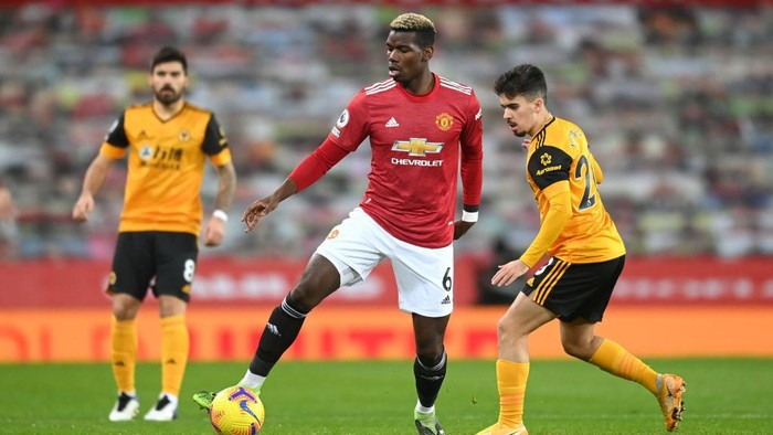 MANCHESTER, ENGLAND - DECEMBER 29: Paul Pogba of Manchester United controls the ball under pressure from Vitinha of Wolverhampton Wanderers during the Premier League match between Manchester United and Wolverhampton Wanderers at Old Trafford on December 29, 2020 in Manchester, England. The match will be played without fans, behind closed doors as a Covid-19 precaution. (Photo by Michael Regan/Getty Images)