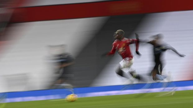 Manchester United's Paul Pogba, center gets past Aston Villa's Matt Targett, right, during the English Premier League soccer match between Manchester United and Aston Villa at Old Trafford in Manchester, England, Friday, Jan. 1, 2021. (Lawrence Griffiths/ Pool via AP)