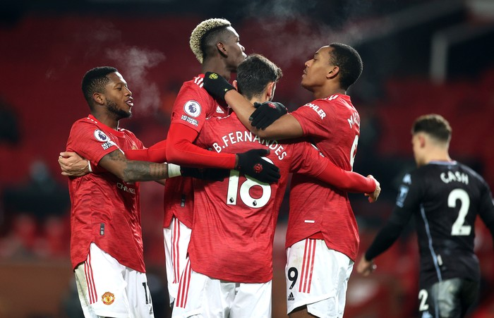 MANCHESTER, ENGLAND - JANUARY 01: Bruno Fernandes of Manchester United celebrates with teammates (L-R) Fred, Paul Pogba and Anthony Martial after scoring their team's second goal  during the Premier League match between Manchester United and Aston Villa at Old Trafford on January 01, 2021 in Manchester, England. The match will be played without fans, behind closed doors as a Covid-19 precaution. (Photo by Carl Recine - Pool/Getty Images)