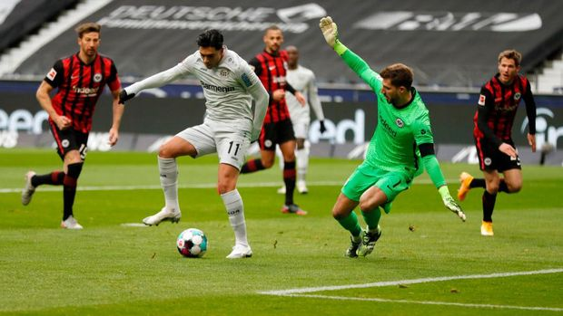 FRANKFURT AM MAIN, GERMANY - JANUARY 02: Nadiem Amiri of Bayer Leverkusen scores their team's first goal past Kevin Trapp of Eintracht Frankfurt during the Bundesliga match between Eintracht Frankfurt and Bayer 04 Leverkusen at Deutsche Bank Park on January 02, 2021 in Frankfurt am Main, Germany. Sporting stadiums around Germany remain under strict restrictions due to the Coronavirus Pandemic as Government social distancing laws prohibit fans inside venues resulting in games being played behind closed doors. (Photo by Ronny Wittek - Pool/Getty Images)