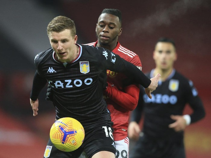 Aston Villas Matt Targett, left holds off the challenge of Manchester Uniteds Aaron Wan-Bissaka during the English Premier League soccer match between Manchester United and Aston Villa at Old Trafford in Manchester, England, Friday, Jan. 1, 2021. (Lawrence Griffiths/ Pool via AP)