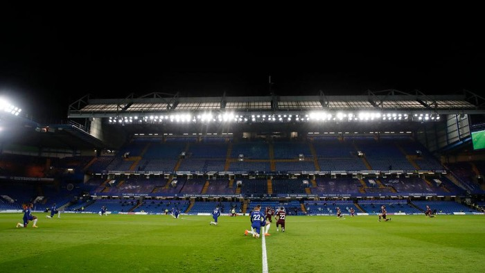 LONDON, ENGLAND - DECEMBER 05: A general view inside the stadium as players and officials take a knee in support of the black lives matter movement during the Premier League match between Chelsea and Leeds United at Stamford Bridge on December 05, 2020 in London, England. A limited number of fans are welcomed back to stadiums to watch elite football across England. This was following easing of restrictions on spectators in tiers one and two areas only. (Photo by Matthew Childs - Pool/Getty Images)