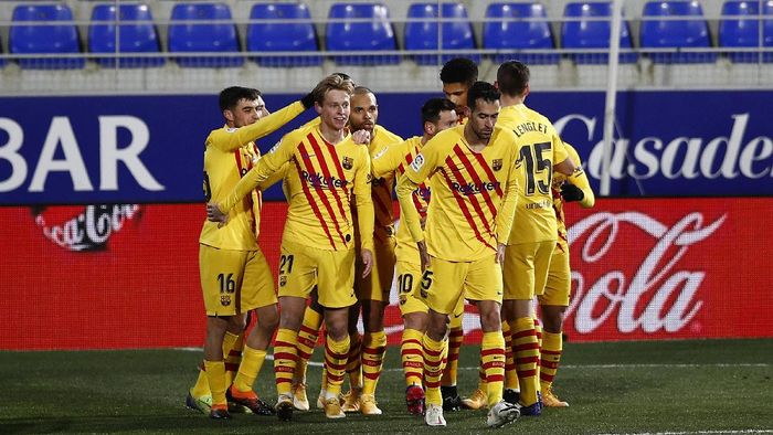 HUESCA, SPAIN - JANUARY 03: Frenkie de Jong of Barcelona  celebrates with teammates Pedri, Martin Braithwaite and Lionel Messi after scoring their teams first goal during the La Liga Santander match between SD Huesca and FC Barcelona at Estadio El Alcoraz on January 03, 2021 in Huesca, Spain. Sporting stadiums around Spain remain under strict restrictions due to the Coronavirus Pandemic as Government social distancing laws prohibit fans inside venues resulting in games being played behind closed doors. (Photo by Eric Alonso/Getty Images)
