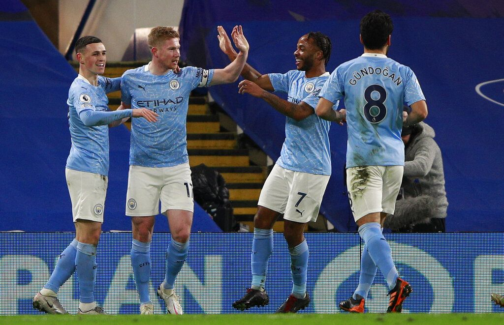 Manchester City's Phil Foden, left, celebrates with teammate Kevin De Bruyne after scoring his side's second goal during the English Premier League soccer match between Chelsea and Manchester City at Stamford Bridge, London, England, Sunday, Jan. 3, 2021. (AP Photo/Ian Walton/Pool)