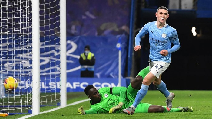 LONDON, ENGLAND - JANUARY 03: Phil Foden of Manchester City celebrates after scoring their sides second goal as Edouard Mendy of Chelsea looks dejected during the Premier League match between Chelsea and Manchester City at Stamford Bridge on January 03, 2021 in London, England. The match will be played without fans, behind closed doors as a Covid-19 precaution. (Photo by Andy Rain - Pool/Getty Images)