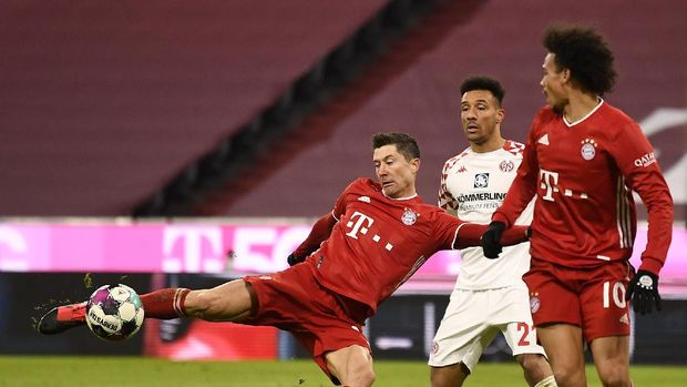 MUNICH, GERMANY - JANUARY 03: Robert Lewandowski of FC Bayern Munich scores their sides fifth goal during the Bundesliga match between FC Bayern Muenchen and 1. FSV Mainz 05 at Allianz Arena on January 03, 2021 in Munich, Germany. Sporting stadiums around Germany remain under strict restrictions due to the Coronavirus Pandemic as Government social distancing laws prohibit fans inside venues resulting in games being played behind closed doors. (Photo by Lukas Barth-Tuttas - Pool/Getty Images)