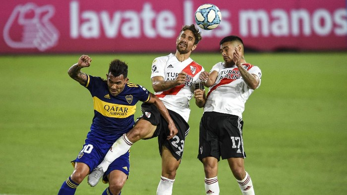 BUENOS AIRES, ARGENTINA - JANUARY 02: (L-R) Carlos Tevez of Boca Juniors jumps for a header with Leonardo Ponzio and Paulo Diaz of River Plate during a match between Boca Juniors and River Plate as part of Zona Campeonato of Copa Diego Maradona 2020 at Estadio Alberto J. Armando on January 02, 2021 in Buenos Aires, Argentina. (Photo by Marcelo Endelli/Getty Images)