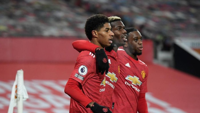 MANCHESTER, ENGLAND - DECEMBER 29: Marcus Rashford of Manchester United celebrates with teammates Paul Pogba and Aaron Wan-Bissaka after scoring his teams first goal during the Premier League match between Manchester United and Wolverhampton Wanderers at Old Trafford on December 29, 2020 in Manchester, England. The match will be played without fans, behind closed doors as a Covid-19 precaution. (Photo by Michael Regan/Getty Images)