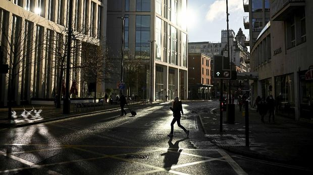 A pedestrian crosses an almost empty street in Manchester, north west England on January 5, 2021, as Britain enters a national lockdown to combat the spread of COVID-19. - England's six-week lockdown, which began at midnight, emulates the first national coronavirus curbs in place from March to June -- but goes further than another instituted in November when schools remained open. Authorities in Wales, Scotland and Northern Ireland have all taken similar measures, putting the UK as a whole in lockdown. (Photo by Oli SCARFF / AFP)