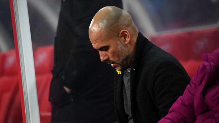 STOKE ON TRENT, ENGLAND - MARCH 12:  Josep Guardiola, Manager of Manchester City adjusts a yellow ribbon prior to the Premier League match between Stoke City and Manchester City at Bet365 Stadium on March 12, 2018 in Stoke on Trent, England.  (Photo by Gareth Copley/Getty Images)