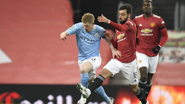 Manchester City's Kevin De Bruyne, left, and Manchester United's Bruno Fernandes fight for the ball during the English League Cup semifinal soccer match between Manchester United and Manchester City at Old Trafford in Manchester, England, Wednesday, Jan. 6, 2021. (Peter Powell/Pool via AP)