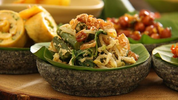 Jukut Urap, the popular Balinese vegetable salad accompanying many Balinese meals. Cooked spinach, long beans, and bean sprouts mixed with spicy grated coconut. Served on a mini stoneware mortar lined with banana leaf, as part of food sampling meal.