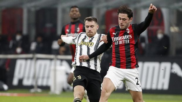 Juventus' Aaron Ramsey, left, duels for the ball with AC Milan's Davide Calabria during the Serie A soccer match between AC Milan and Juventus at the San Siro stadium, in Milan, Italy, Wednesday, Jan. 6, 2021. (AP Photo/Antonio Calanni)