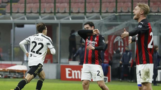 Juventus' Federico Chiesa, left, celebrates after scoring his side's second goal during the Serie A soccer match between AC Milan and Juventus at the San Siro stadium, in Milan, Italy, Wednesday, Jan. 6, 2021. (AP Photo/Antonio Calanni)