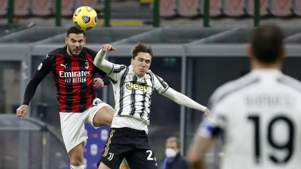 AC Milan's Theo Hernandez, left, jumps for the ball with Juventus' Federico Chiesa during the Serie A soccer match between AC Milan and Juventus at the San Siro stadium, in Milan, Italy, Wednesday, Jan. 6, 2021. (AP Photo/Antonio Calanni)