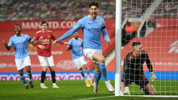 MANCHESTER, ENGLAND - JANUARY 06: John Stones of Manchester City celebrates after scoring their team's first goal during the Carabao Cup Semi Final match between Manchester United and Manchester City at Old Trafford on January 06, 2021 in Manchester, England. The match will be played without fans, behind closed doors as a Covid-19 precaution. (Photo by Shaun Botterill/Getty Images)
