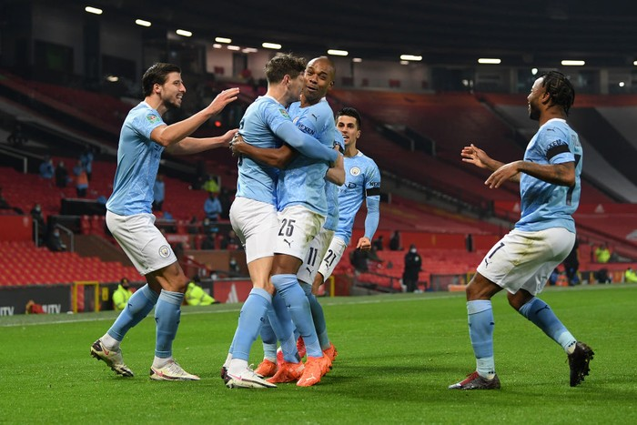 MANCHESTER, ENGLAND - JANUARY 06: John Stones of Manchester City celebrates with (l-r) Ruben Dias, Fernandinho, Ferran Torres and Raheem Sterling of Manchester City after scoring his sides 1st goal during the Carabao Cup Semi Final match between Manchester United and Manchester City at Old Trafford on January 06, 2021 in Manchester, England. The match will be played without fans, behind closed doors as a Covid-19 precaution. (Photo by Shaun Botterill/Getty Images)