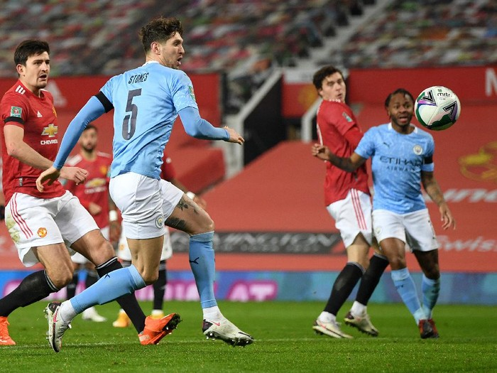 MANCHESTER, ENGLAND - JANUARY 06: John Stones of Manchester City scores their teams first goal during the Carabao Cup Semi Final match between Manchester United and Manchester City at Old Trafford on January 06, 2021 in Manchester, England. The match will be played without fans, behind closed doors as a Covid-19 precaution. (Photo by Shaun Botterill/Getty Images)