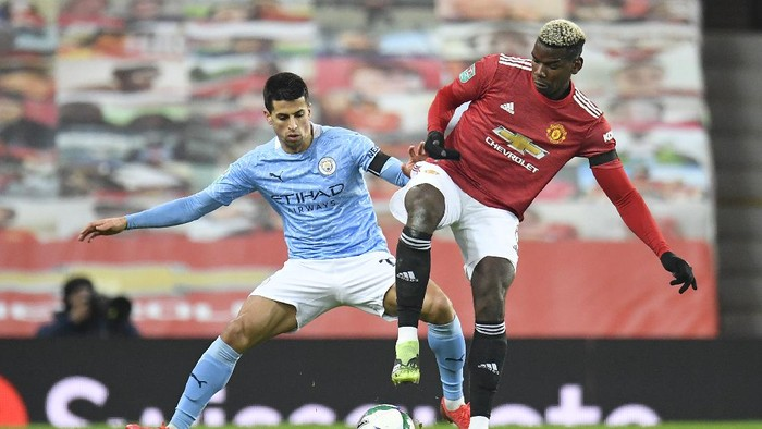 MANCHESTER, ENGLAND - JANUARY 06: Joao Cancelo of Manchester City battles for possession with Paul Pogba of Manchester United during the Carabao Cup Semi Final match between Manchester United and Manchester City at Old Trafford on January 06, 2021 in Manchester, England. The match will be played without fans, behind closed doors as a Covid-19 precaution. (Photo by Peter Powell - Pool/Getty Images)