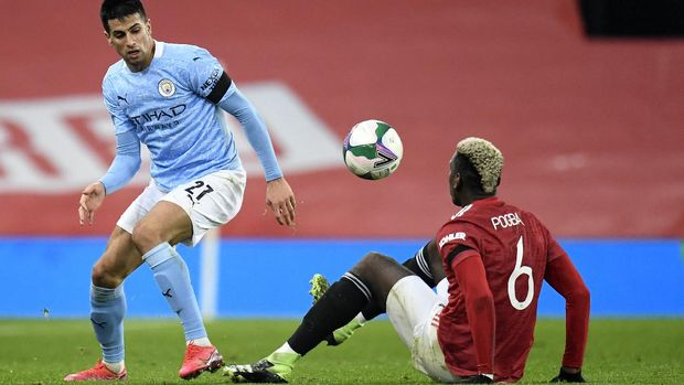 Manchester United's Paul Pogba, bottom, and Manchester City's Joao Cancelo fight for the ball during the English League Cup semifinal soccer match between Manchester United and Manchester City at Old Trafford in Manchester, England, Wednesday, Jan. 6, 2021. (Peter Powell/Pool via AP)