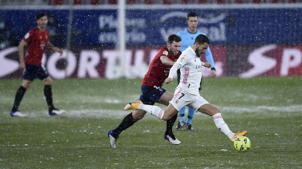 PAMPLONA, SPAIN - JANUARY 09: Eden Hazard of Real Madrid is challenged by Jon Moncayola of Osasuna during the La Liga Santander match between C.A. Osasuna and Real Madrid at Estadio El Sadar on January 09, 2021 in Pamplona, Spain. Sporting stadiums around Spain remain under strict restrictions due to the Coronavirus Pandemic as Government social distancing laws prohibit fans inside venues resulting in games being played behind closed doors. (Photo by Juan Manuel Serrano Arce/Getty Images)