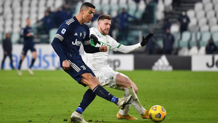 TURIN, ITALY - JANUARY 10: Cristiano Ronaldo of Juventus F.C.  scores their teams third goal under pressure from Georgios Kyriakopoulos of Sassuolo during the Serie A match between Juventus and US Sassuolo at Allianz Stadium on January 10, 2021 in Turin, Italy. Sporting stadiums around Italy remain under strict restrictions due to the Coronavirus Pandemic as Government social distancing laws prohibit fans inside venues resulting in games being played behind closed doors. (Photo by Valerio Pennicino/Getty Images )