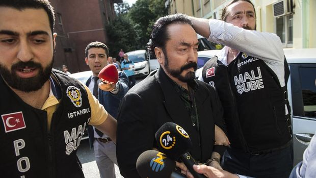 Turkish police officers escort televangelist and leader of a sect, Adnan Oktar (C) on July 11, 2018, in Istanbul, as he is arrested on fraud charges. - Turkish police detained the televangelist on fraud charges on July 11, 2018, notorious for propagating conservative views while surrounded by scantily-clad women he refers to as his
