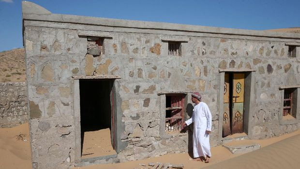 Mohammed al-Ghanbousi, a former inhabitant of Wadi al-Murr, stands next to his abandoned house in the Omani village, about 400 kms (250 miles) southwest of the capital Muscat, on December 31, 2020. - Encroaching desert sands have left little evidence that Wadi al-Murr ever existed, but former inhabitants, while resigned to its destruction, are trying to preserve its memory. The advance of the desert is not specific to the sultanate of Oman, and experts say climate change is one of the factors propelling the phenomenon in different parts of the world. (Photo by MOHAMMED MAHJOUB / AFP)