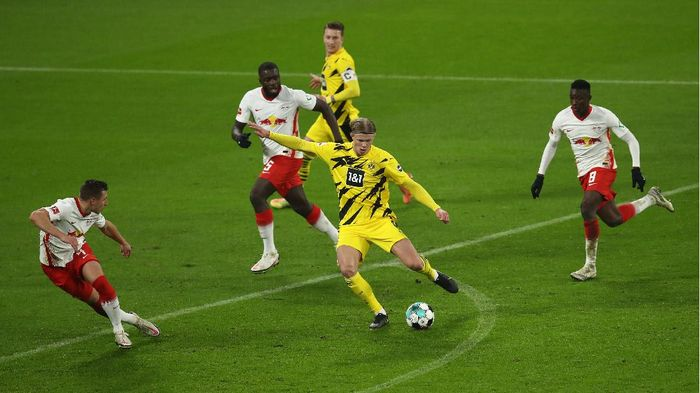 LEIPZIG, GERMANY - JANUARY 09: Erling Haland of Borussia Dortmund shoots at goal under pressure from Dayot Upamecano and Amadou Haidara during the Bundesliga match between RB Leipzig and Borussia Dortmund at Red Bull Arena on January 09, 2021 in Leipzig, Germany. Sporting stadiums around Germany remain under strict restrictions due to the Coronavirus Pandemic as Government social distancing laws prohibit fans inside venues resulting in games being played behind closed doors. (Photo by Maja Hitij/Getty Images)