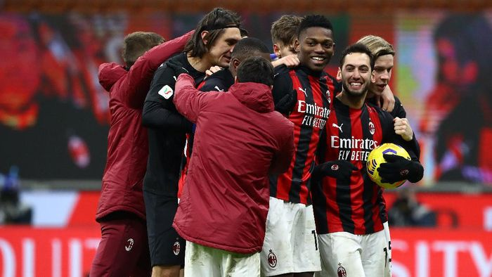 MILAN, ITALY - JANUARY 12: Hakan Calhanoglu of A.C. Milan celebrates with Rafael Leao after scoring the winning penalty during a penalty shoot out during the Coppa Italia match between AC Milan and Torino FC at Stadio Giuseppe Meazza on January 12, 2021 in Milan, Italy. Sporting stadiums around Italy remain under strict restrictions due to the Coronavirus Pandemic as Government social distancing laws prohibit fans inside venues resulting in games being played behind closed doors. (Photo by Marco Luzzani/Getty Images)