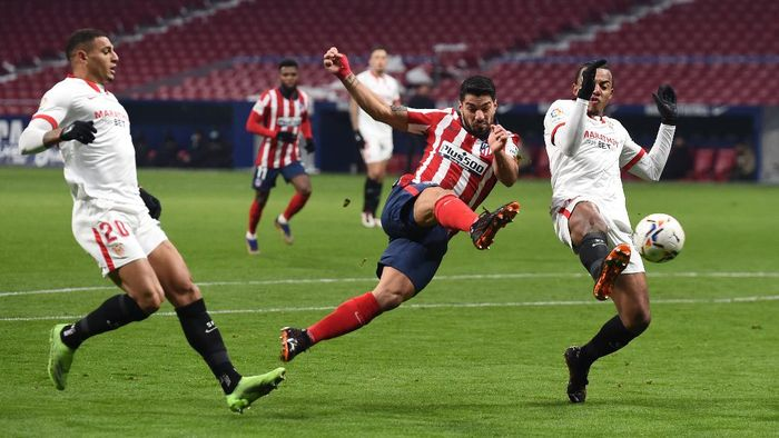 MADRID, SPAIN - JANUARY 12: Luis Suarez of Atletico de Madrid shoots as Jules Kounde of Sevilla FC attempts to block during the La Liga Santander match between Atletico de Madrid and Sevilla FC at Estadio Wanda Metropolitano on January 12, 2021 in Madrid, Spain. Sporting stadiums around Spain remain under strict restrictions due to the Coronavirus Pandemic as Government social distancing laws prohibit fans inside venues resulting in games being played behind closed doors. (Photo by Denis Doyle/Getty Images)