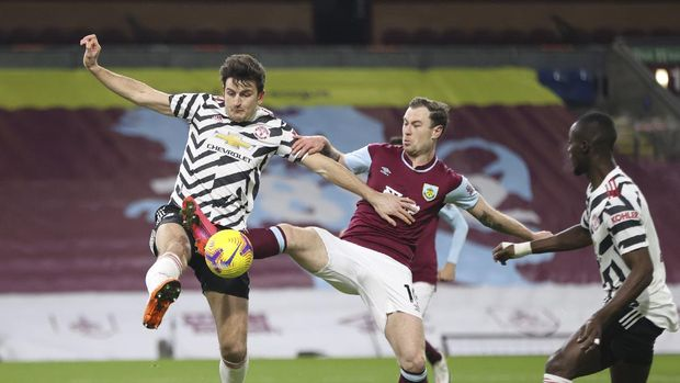 Manchester United's Harry Maguire, left, fights for the ball with Burnley's Ashley Barnes, right, during the English Premier League soccer match between Burnley and Manchester United in Burnley, England, Tuesday, Jan. 12, 2021. (Clive Brunskill/Pool via AP)