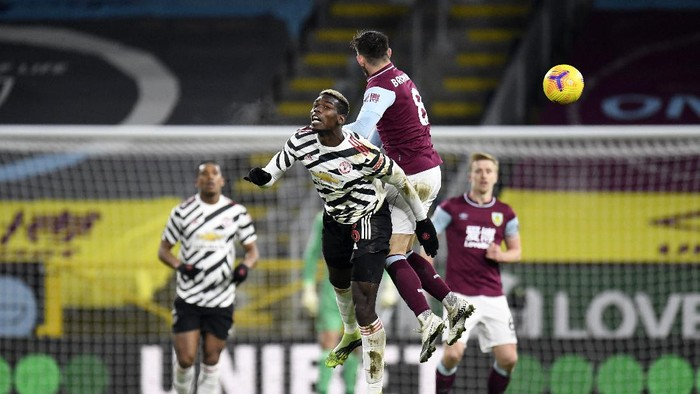 BURNLEY, ENGLAND - JANUARY 12: Paul Pogba of Manchester United and Josh Brownhill of Burnley contest a header during the Premier League match between Burnley and Manchester United at Turf Moor on January 12, 2021 in Burnley, England. Sporting stadiums around England remain under strict restrictions due to the Coronavirus Pandemic as Government social distancing laws prohibit fans inside venues resulting in games being played behind closed doors. (Photo by Peter Powell - Pool/Getty Images)