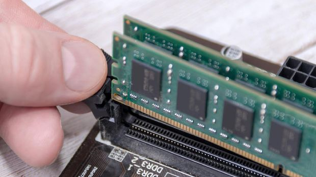 Hand removing DDR RAM - computer memory - part of a desktop computer + logos and ref numbers removed