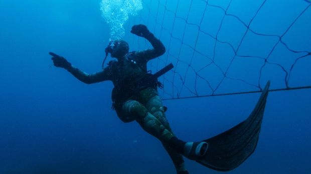 Shark activist Walter Bernardis swims along a shark net during a dive in Umkomaas near Durban, South Africa, on December 10, 2020. - Today, on more than 300km of KwaZulu-Natal coast, 37 beaches are equipped with a controversial shark control system, made of shark nets -  two parallel rows of submerged mesh net - and drum lines - an aquatic trap used to lure and capture large sharks using baited hooks - both placed around beaches to reduce shark attacks on swimmers. Although there has not been any mortal attack for 67 years, every year at least 400 sharks have been killed by this system, prompting environmentalists to criticise it for its ecological danger. (Photo by Michele Spatari / AFP)