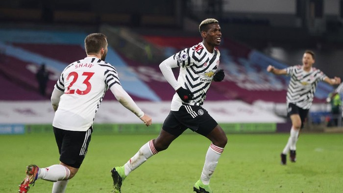 BURNLEY, ENGLAND - JANUARY 12: Paul Pogba of Manchester United celebrates with Luke Shaw (L) after scoring their teams first goal during the Premier League match between Burnley and Manchester United at Turf Moor on January 12, 2021 in Burnley, England. Sporting stadiums around England remain under strict restrictions due to the Coronavirus Pandemic as Government social distancing laws prohibit fans inside venues resulting in games being played behind closed doors. (Photo by Clive Brunskill/Getty Images)