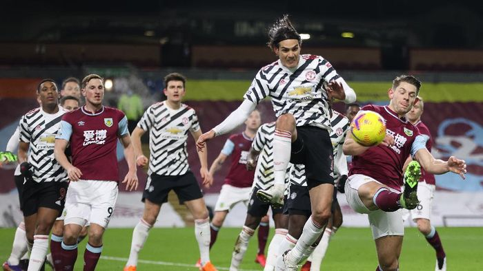 BURNLEY, ENGLAND - JANUARY 12: Edinson Cavani of Manchester United battles for possession with James Tarkowski of Burnley during the Premier League match between Burnley and Manchester United at Turf Moor on January 12, 2021 in Burnley, England. Sporting stadiums around England remain under strict restrictions due to the Coronavirus Pandemic as Government social distancing laws prohibit fans inside venues resulting in games being played behind closed doors. (Photo by Clive Brunskill/Getty Images)