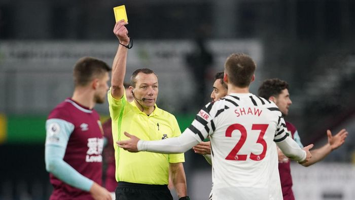 BURNLEY, ENGLAND - JANUARY 12: Referee, Kevin Friend shows Luke Shaw of Manchester United a yellow card during the Premier League match between Burnley and Manchester United at Turf Moor on January 12, 2021 in Burnley, England. Sporting stadiums around England remain under strict restrictions due to the Coronavirus Pandemic as Government social distancing laws prohibit fans inside venues resulting in games being played behind closed doors. (Photo by Jon Super - Pool/Getty Images)