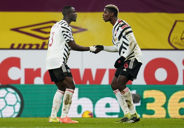 BURNLEY, ENGLAND - JANUARY 12: Paul Pogba of Manchester United celebrates with Eric Bailly after scoring their teams first goal during the Premier League match between Burnley and Manchester United at Turf Moor on January 12, 2021 in Burnley, England. Sporting stadiums around England remain under strict restrictions due to the Coronavirus Pandemic as Government social distancing laws prohibit fans inside venues resulting in games being played behind closed doors. (Photo by Jon Super - Pool/Getty Images)