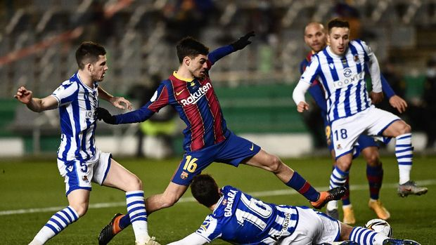 Barcelona's Pedri, center, battles for the ball with Real Sociedad defenders during Spanish Super Cup semi final soccer match between Barcelona and Real Sociedad at Nuevo Arcangel stadium in Cordoba, Spain, Wednesday, Jan. 13, 2021. (AP Photo/Jose Breton)