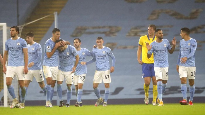Manchester City players celebrate after Manchester Citys Phil Foden, centre, scored his sides opening goal during the English Premier League soccer match between Manchester City and Brighton and Hove Albion at the Etihad Stadium in Manchester, England, Wednesday, Jan. 13, 2021. (Martin Rickett /Pool via AP)
