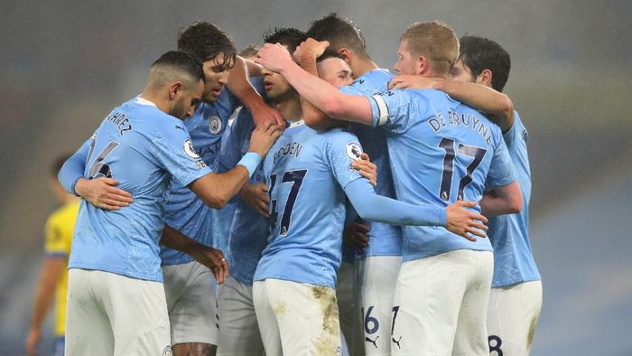 MANCHESTER, ENGLAND - JANUARY 13: Phil Foden of Manchester City celebrates with teammates Rodrigo, Kevin De Bruyne and Ilkay Guendogan after scoring their teams first goal during the Premier League match between Manchester City and Brighton & Hove Albion at Etihad Stadium on January 13, 2021 in Manchester, England. Sporting stadiums around England remain under strict restrictions due to the Coronavirus Pandemic as Government social distancing laws prohibit fans inside venues resulting in games being played behind closed doors. (Photo by Clive Brunskill/Getty Images)