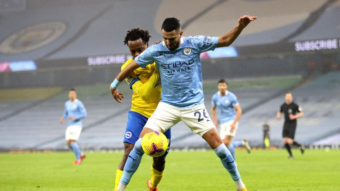 MANCHESTER, ENGLAND - JANUARY 13: Riyad Mahrez of Manchester City battles for possession with Percy Tau of Brighton and Hove Albion during the Premier League match between Manchester City and Brighton & Hove Albion at Etihad Stadium on January 13, 2021 in Manchester, England. Sporting stadiums around England remain under strict restrictions due to the Coronavirus Pandemic as Government social distancing laws prohibit fans inside venues resulting in games being played behind closed doors. (Photo by Clive Brunskill/Getty Images)